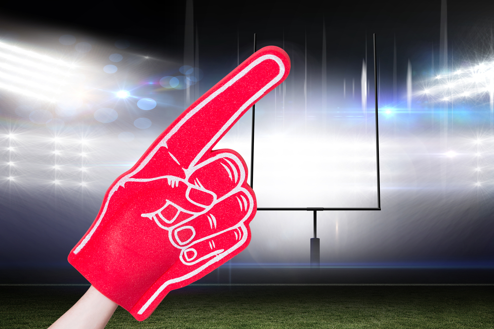 American football player holding supporter foam hand against american football arena