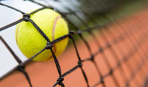 Tennis ball stuck on the net at a clay court