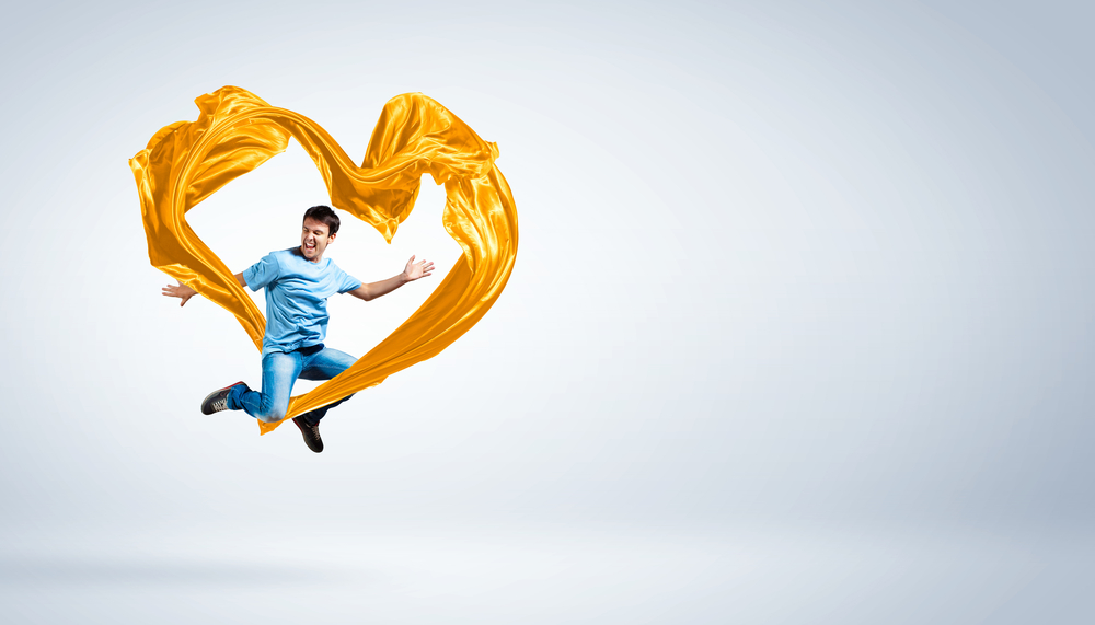 Young man dancing with yellow fabric over white background